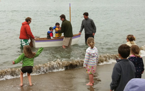 A small boat floating in the water with two children in it.