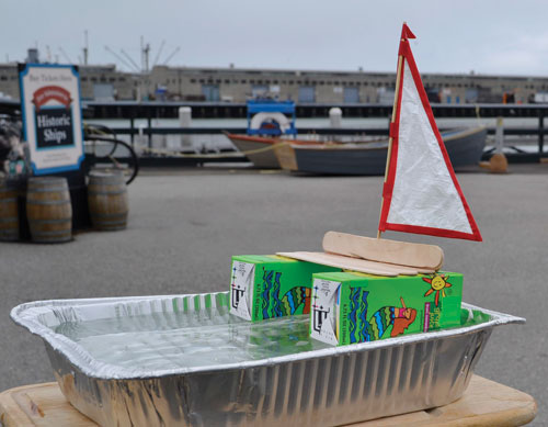 A boat made out of juice boxes and sticks floating in a roasting pan filled with water.