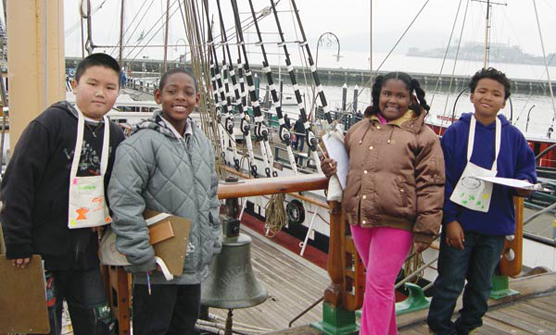 Four elementary school students standing on the deck of the sailing ship BALCLUTHA.
