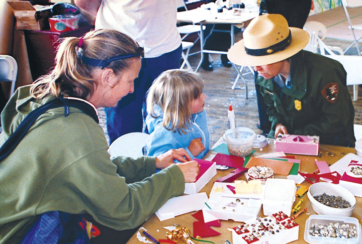A park ranger at a table with a child doing maritime crafts.