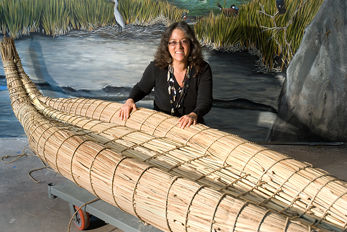 A woman sitting behind a canoe made out of tule reeds. She has her hands resting on the tan-colored canoe.