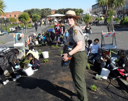 A park ranger standing in the middle of an empty garden plot with kids planting native plants behind her.