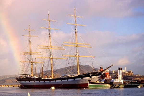A three-masted historic ship moored at a pier.