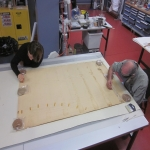 Two onservators cleaning the Bendixsen drawing