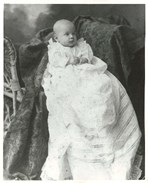 Black and white photo of the baby seated in a chair in a long white gown
