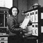 A woman standing in front of a file cabinet.