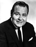 Black and white publicity portrait of Jonthan Winters in a black suit