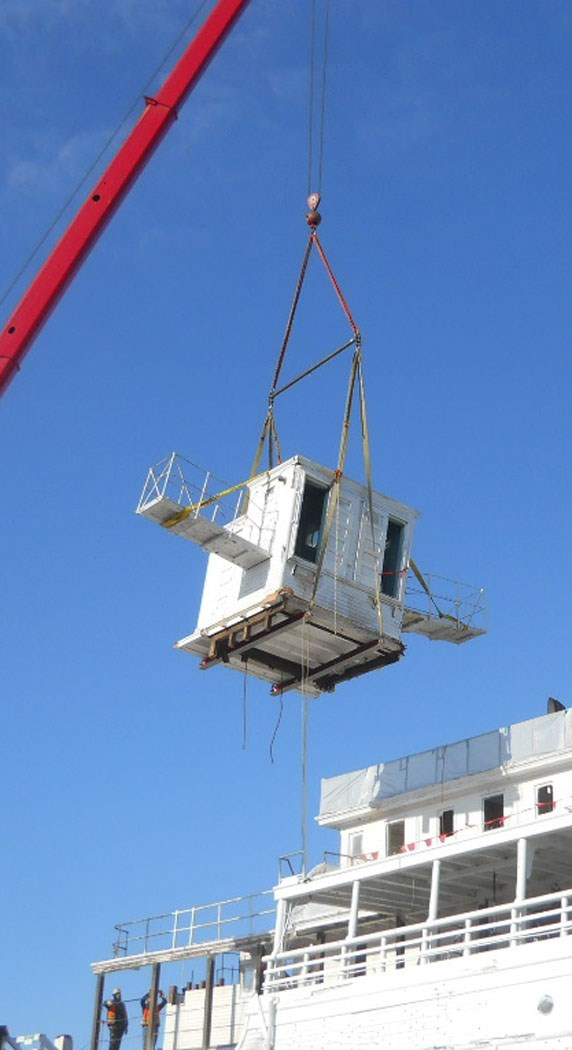 The pilothouse hanging from a crane.