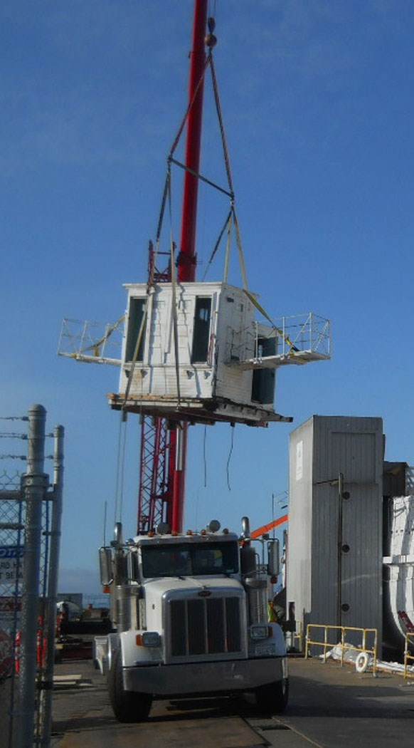 The pilothouse being lowered onto a truck.