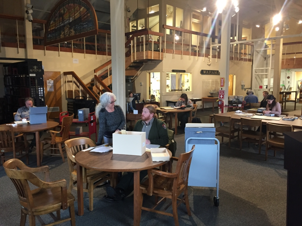View of the reading room in the Maritime Research Center showing researchers, NPS uniformed staff as well as visitors, at tables consulting archives, books, and audio materials, Reference Librarian Gina Bardi at the Reference Desk in the background