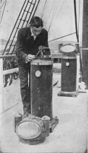 Black and white photograph of James Percy Ault bending over and handling scientific instrument