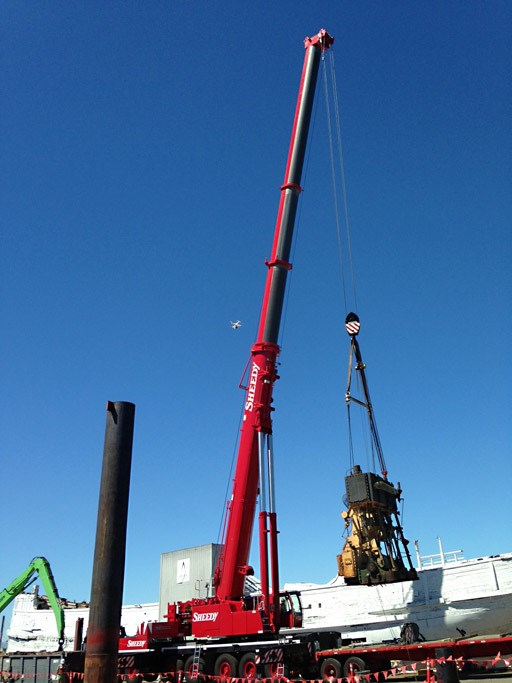 A red crane lifting a large engine off a ship.