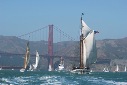 The scow schooner ALMA with sails set, running with the wind on San Francisco Bay, with the Golden Gate Bridge and Marin Headlands in the background.