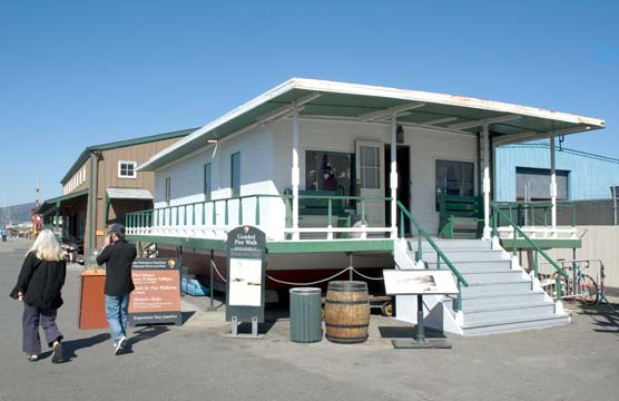 A wooden houseboat painted white with green trim, a front porch, and sitting on dry land.