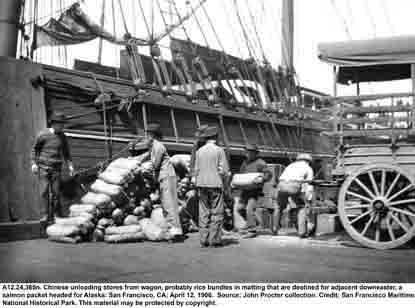 A black and white photo taken in 1906 of a San Francisco pier. Chinese men are unloading rice wrapped in matting from a cart.