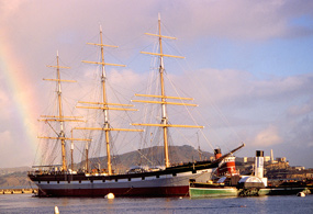 The majestic three-masted historic ship BALCLUTHA with a rainbow off her aft port quarter.