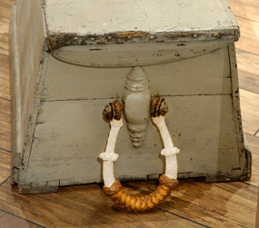 One end of a sailor's sea chest with a rope handle attached to the side.