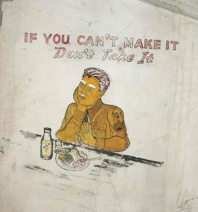 Mural painted on a plaster wall depicing a solider in a World War II uniform eating meal.