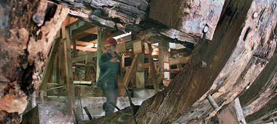 Below decks photo of ship worker looking at ravages of dry rot to Thayer's timbers.