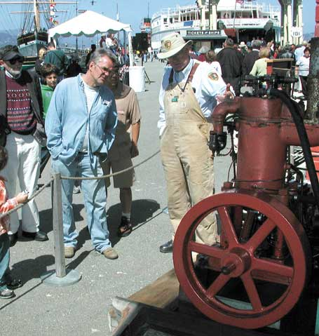 A volunteer showing a Hicks engine to a visitor on Hyde Street Pier.