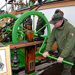 A park ranger turning the handle of a pump on the deck of Balclutha.