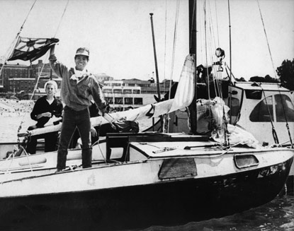 A young man standing on the deck of a small sailboat and waving.