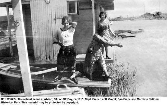 A black and white photo of three women standing on the deck of a houseboat.