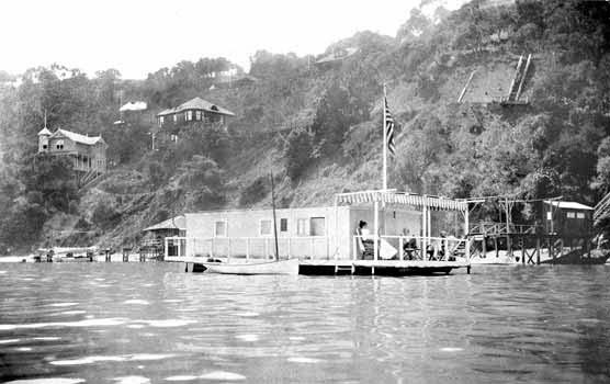 A black and white photo showing a flat-roofed houseboat moored in a cove with a hillside behind it.