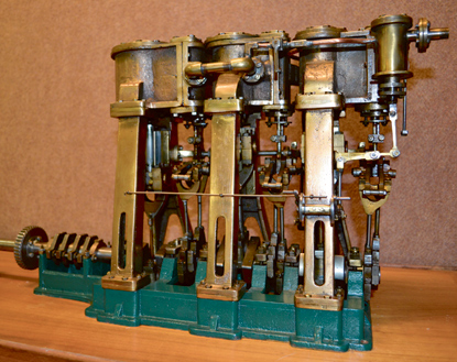 A scale model of a steam engine made of brass and steel.