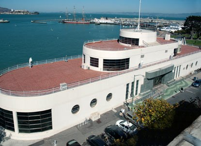 A large, ship-shaped building with a red roof on the SF Bay shoreline.