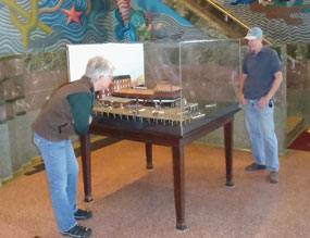Two visitors in the Maritime Museum lobby looking at a diorama of a ship.