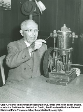 Otto Fischer seated at a desk with an 1885 prototype of the Regan Vapor engine sitting on the tabletop.