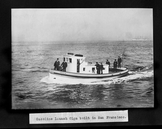 A motor boat on the water with seven men in dark suits riding on the deck.