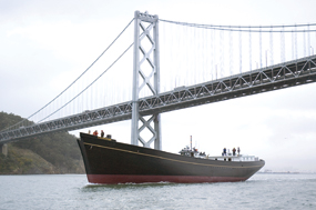 A large, wooden ship passing underneath the Bay Bridge.