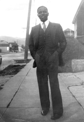 Thomas Fleming standing on sidewalk, wearing a three piece suit and smiling.