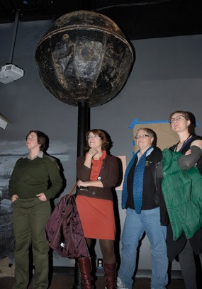 Four people standing near a large sphere atop a pole.