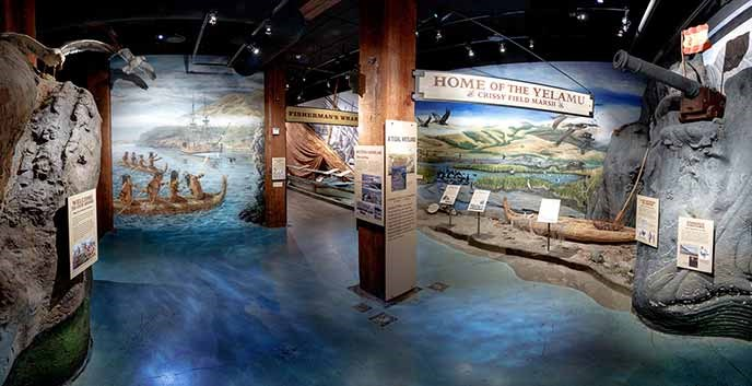 The entrance to an exhibit in the visitor center with blue-colored flooring and murals painted on the walls.