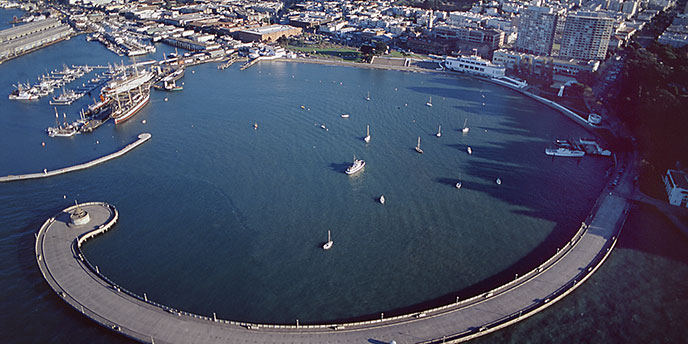 An aerial view of the park showing the curving Municipal Pier enclosing Aquatic Park cove. Hyde Street Pier and the fleet of historic vessels is on the left.