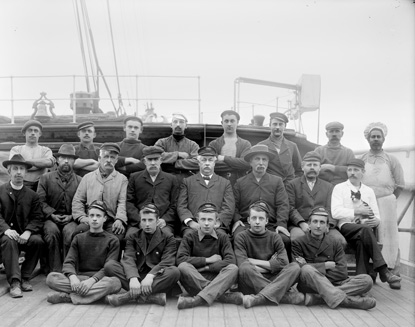 Twenty one men seated on the deck of a sailing ship for a formal pose of the ship's crew..