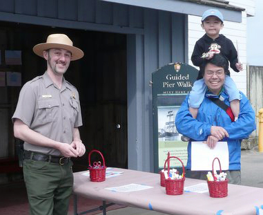 A park ranger standing next to an adult carrying a child on his shoulders.