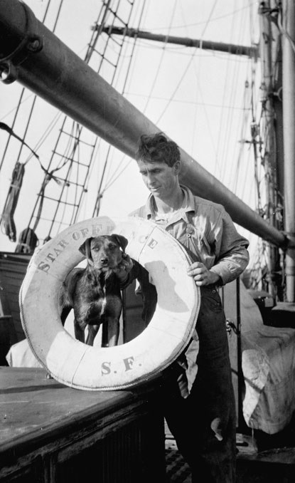 A man standing on the deck of a ship holding a ship's ring around his black-colored dog.