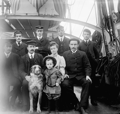 Family members, crew and large dog posing for a formal portrait on the deck of a large sailing ship.
