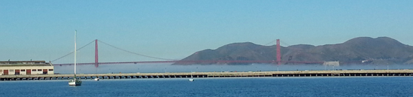 The Golden Gate Bridge with fog forming below the main deck.