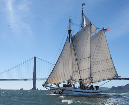 Scow schooner ALMA with her sails raised on San Francisco Bay with the Golden Gate Bridge in the background.
