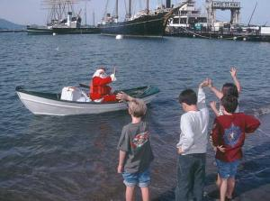 Children standing on a beach waving to Santa Claus in a rowboat with Hyde Street Pier in the background.
