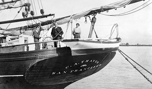 The stern of a lumber schooner with two men and a woman standing on the deck.