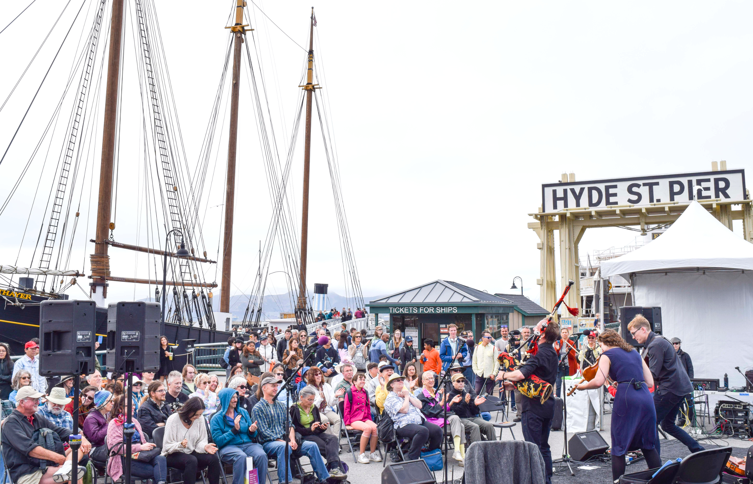 Crowd of people sitting in folding chairs and standing to watch a band perform on a stage near the Eureka ferryboat gangway.