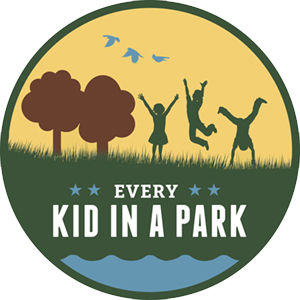 A round logo with trees and kids jumping.