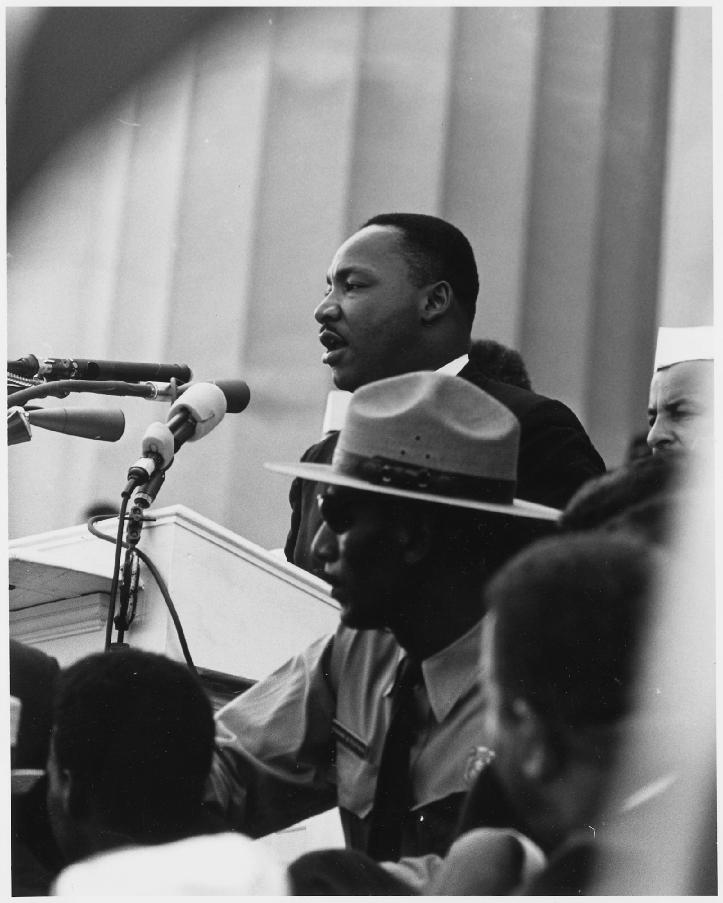 "Dr. Martin Luther King, Jr. delivers his ""I Have A Dream"" speech from a podium with a National Park Service ranger in the foreground"