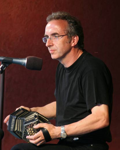 A man seated in front of a microphone and holding a musical instrument that looks like a small accordion.